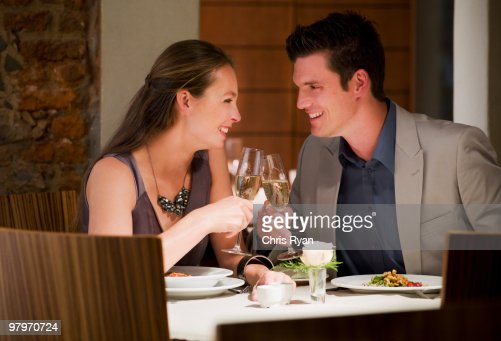 Couple toasting champagne glasses at restaurant table : ストックフォト