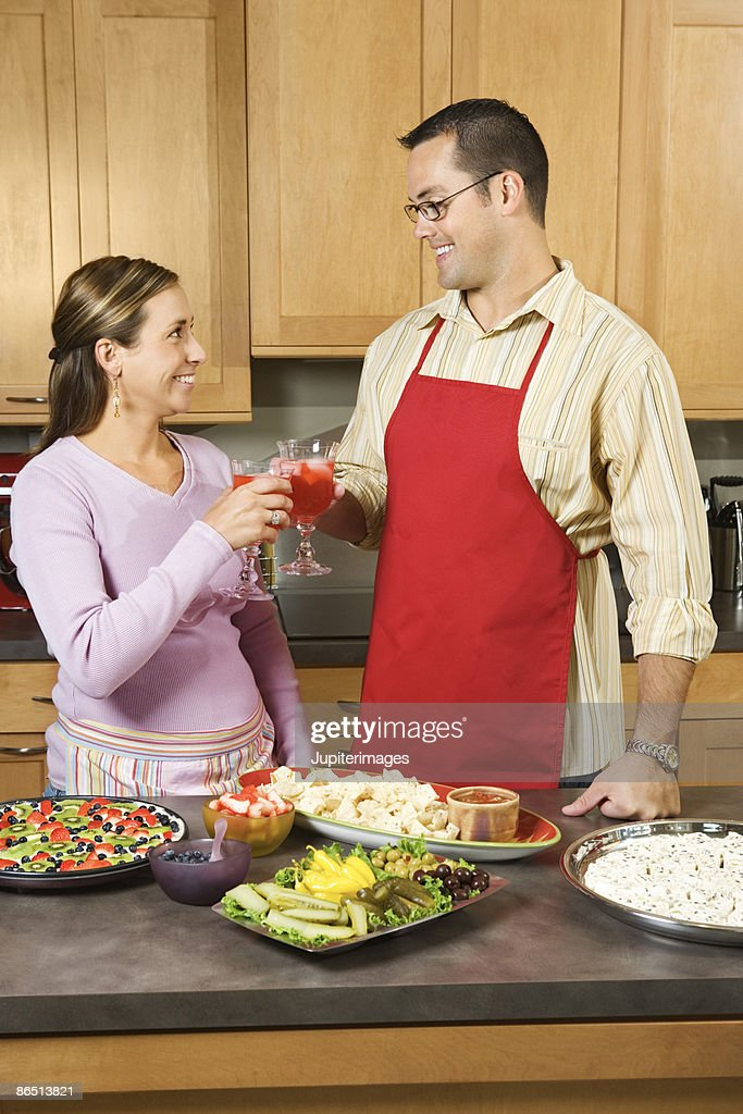 Couple toasting drinks in kitchen : Stock Photo
