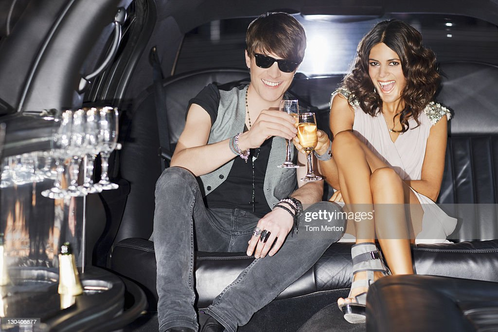 Couple toasting each other in limo : Stock Photo