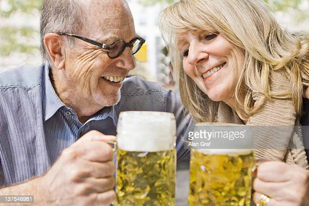 Couple portant un toast les autres, avec de la bière