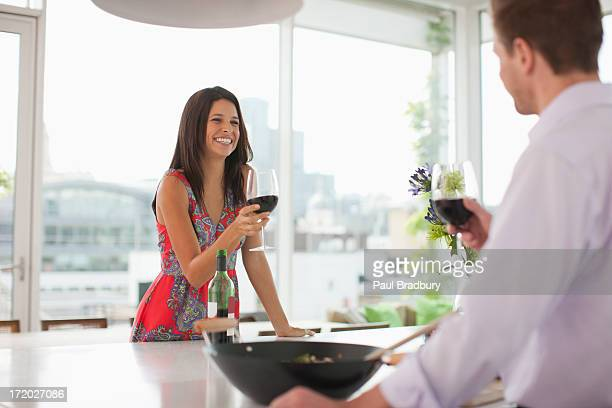 Couple dans la cuisine avec un toast de vin rouge