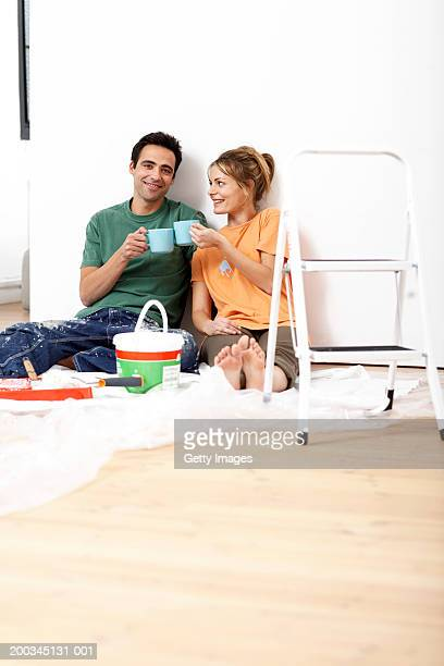Couple toasting mugs, sitting on floor by paint and step ladder