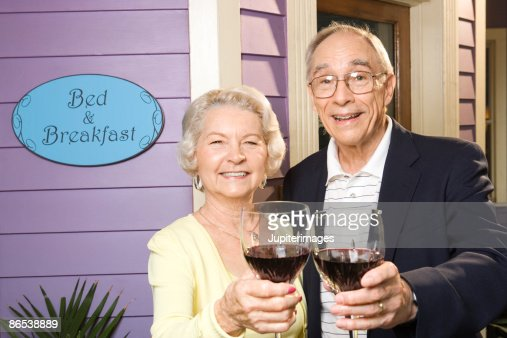 Couple toasting wine glasses outside of bed and breakfast