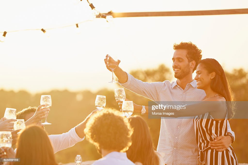 Couple toasting wine glasses with friends