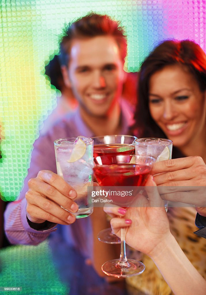 Couple toasting with friends in a nightclub : Stock Photo