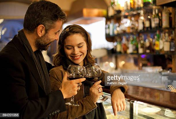 couple toasting with red wine at bar