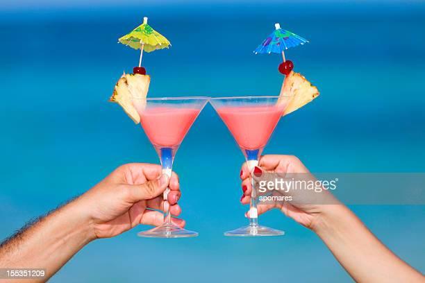 Coppia brindando con cocktail tropicale su una spiaggia Turchese