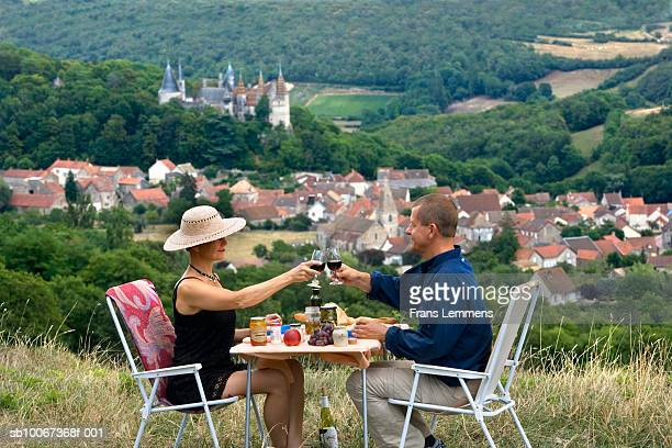 Couple toasting with wing, Castle and village of La Rochepot in background, side view