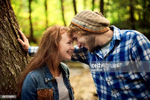 Couple touching foreheads in forest