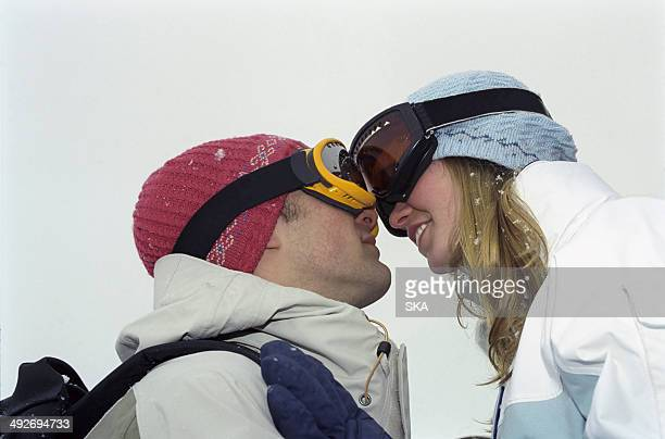 Couple touching heads wearing goggles on