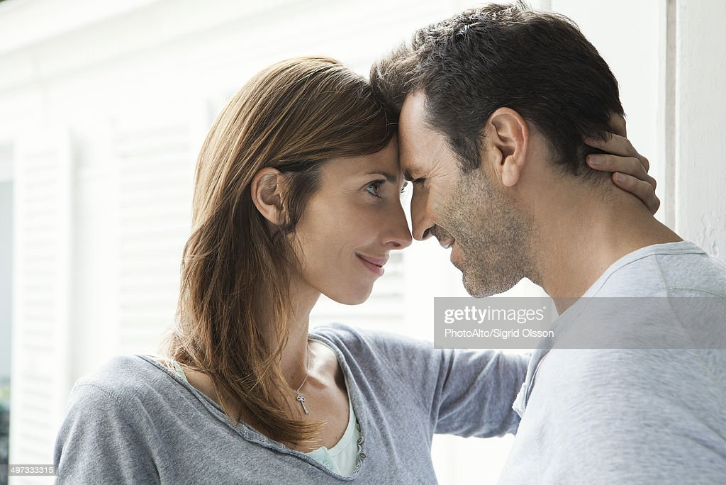 Couple touching noses by window