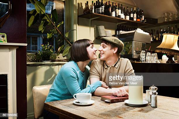 Couple touching noses, sitting in cafe.