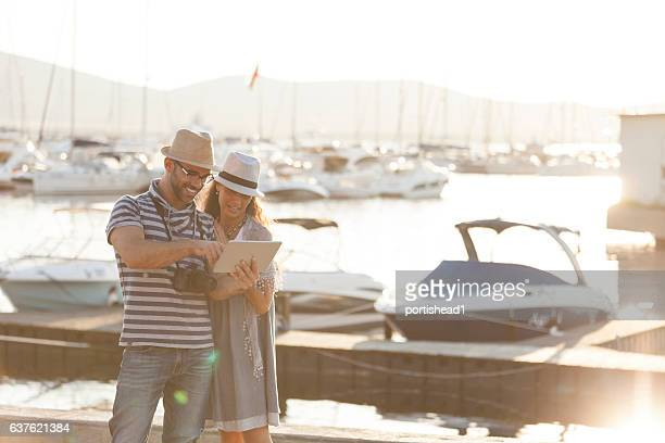 Couple tourists using digital tablet on harbor