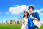 couple take world map adn travel to stonehenge