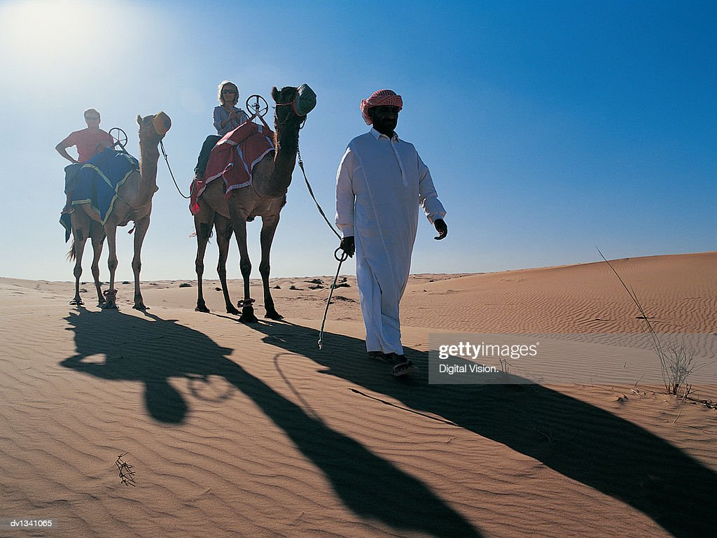 Couple Travelling Across the Desert on Camel Following a Man Wearing Traditional Middle Eastern Dress