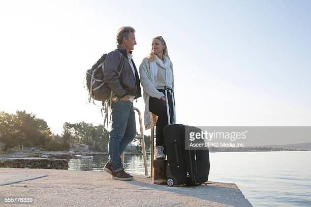 Couple travelling with luggage wait at ferry dock
