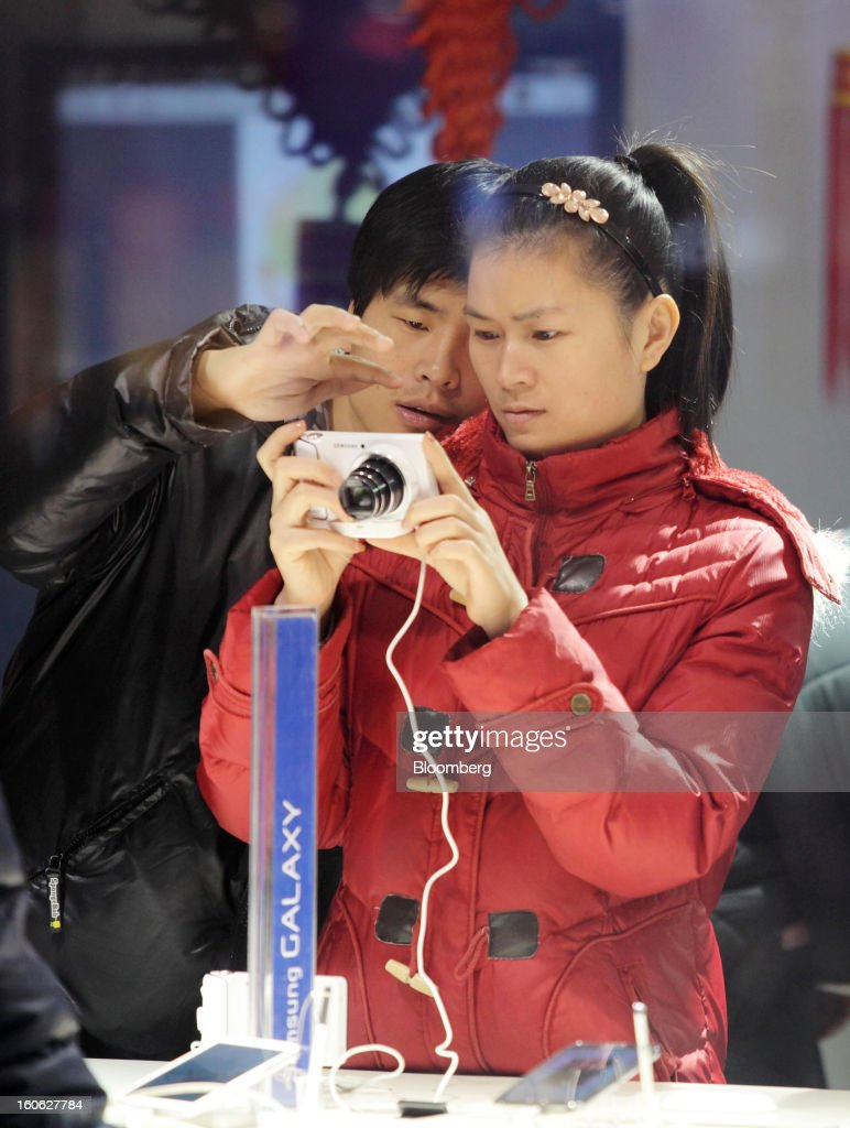 A couple tries a Samsung Electronics Co. digital camera at the company's store in the East Nanjing Road shopping area of Shanghai, China, on Friday, Feb. 1, 2013. China's services industries grew at the fastest pace since August as gains in retailing and construction aid government efforts to drive a recovery in the world's second-biggest economy. Photographer: Tomohiro Ohsumi/Bloomberg via Getty Images