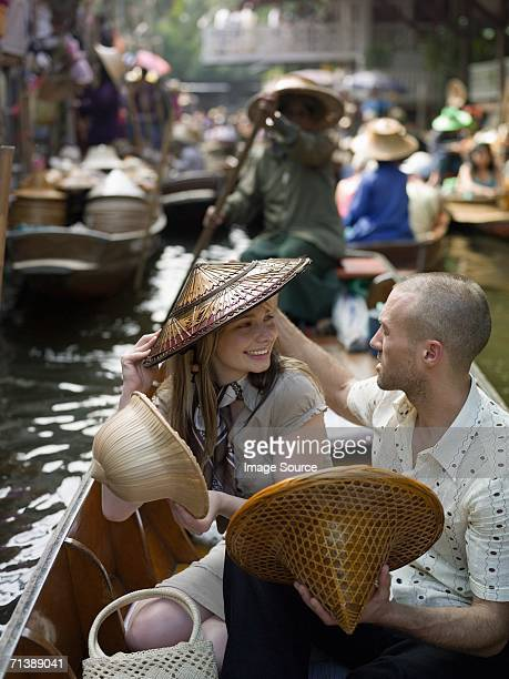 Paar anprobieren Hüte im floating market
