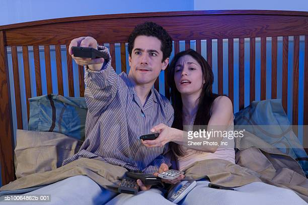 Couple trying several remote controls in bed