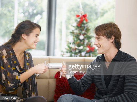 Couple tugging on Christmas cracker : Stock Photo