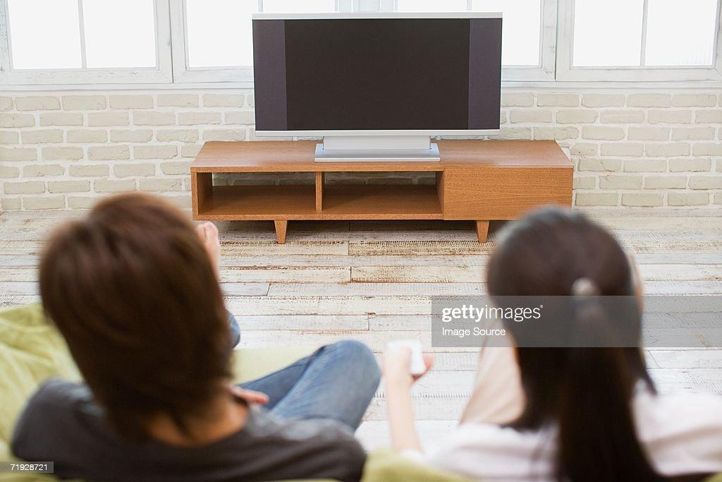 Couple turning television on : Stock Photo