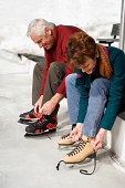 Couple tying ice skates