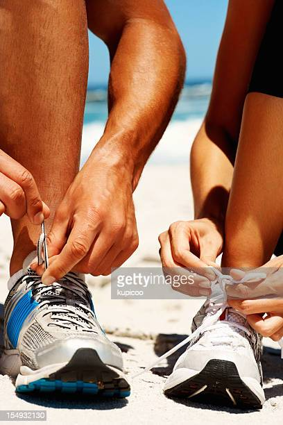 Couple tying their shoes before jogging