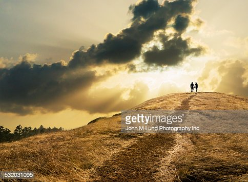 Couple under dramatic clouds over grassy rural hill
