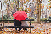 couple under umbrella in autumn park, love concept, happy elderly people