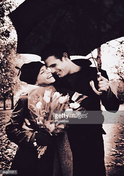 Couple under umbrella in park