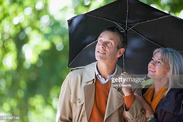 Couple under umbrella looking up