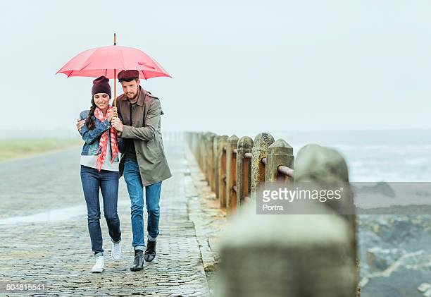 Couple under umbrella walking at seaside