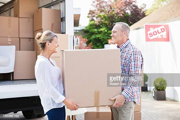Couple unloading box from moving van
