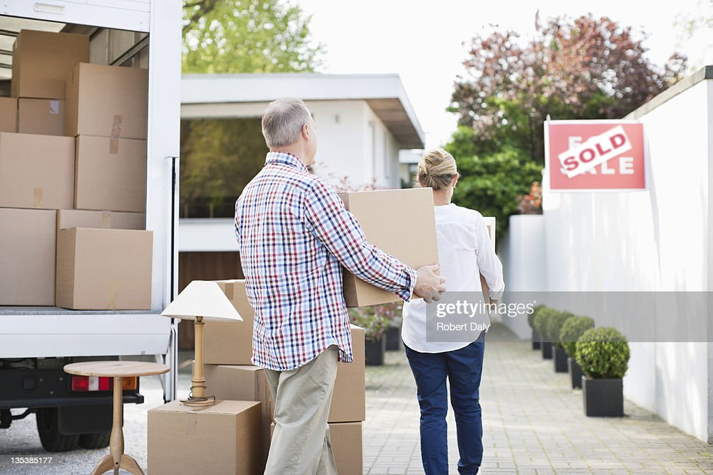 Couple unloading boxes from moving van : Stock Photo
