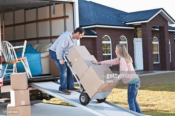 Couple unloading boxes from moving van