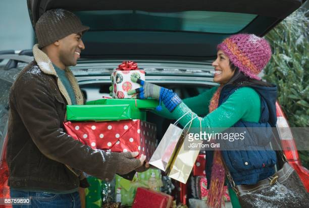 Couple unloading Christmas presents from car trunk