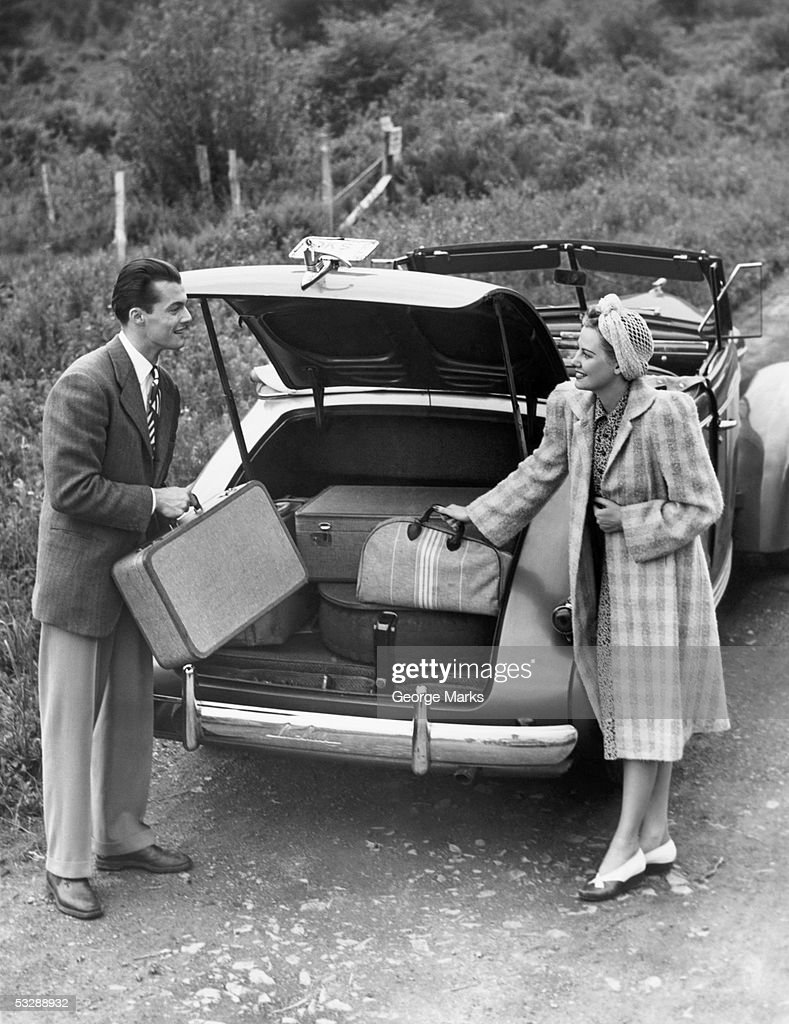 Couple unloading luggage from trunk of c : Stock Photo