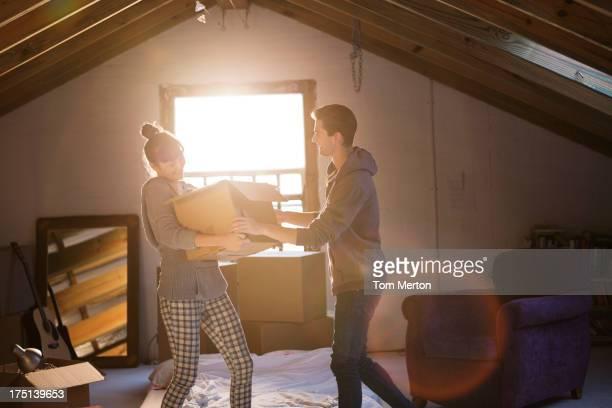Couple unpacking box in attic