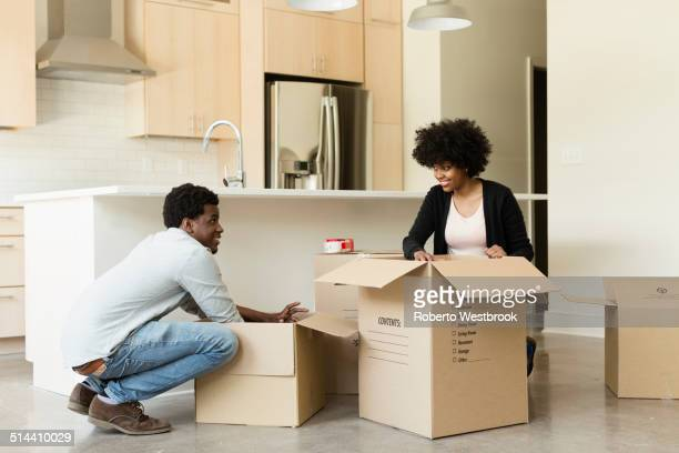 Couple unpacking cardboard box in new house