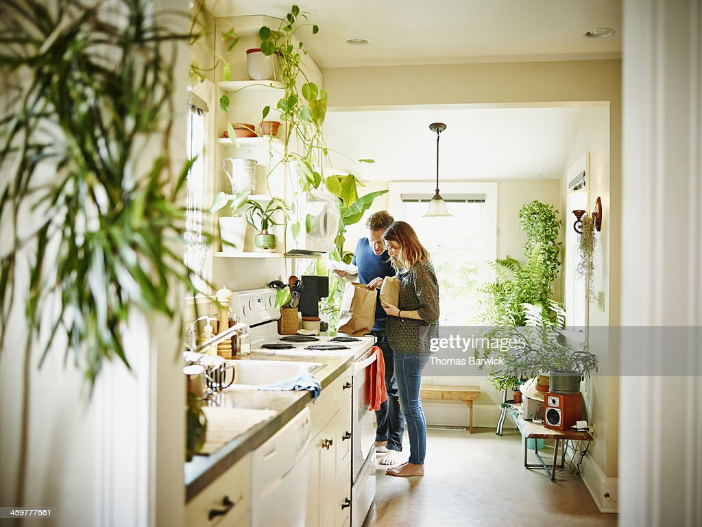 Couple unpacking groceries in kitchen of home