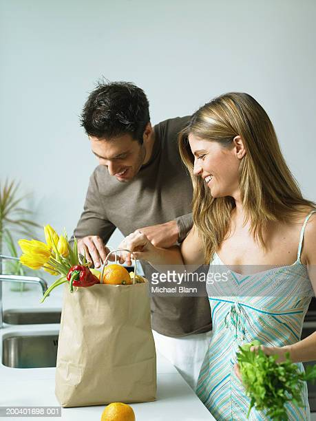 Couple unpacking groceries in kitchen, smiling