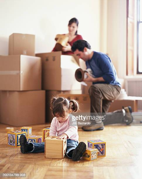 Couple unpacking in new home, girl (2-4) playing on floor