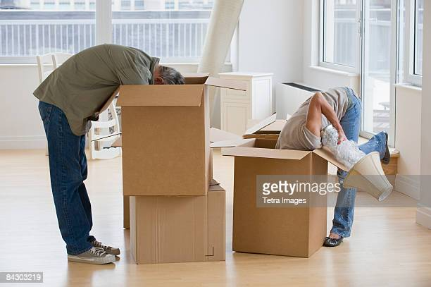 Couple unpacking moving boxes