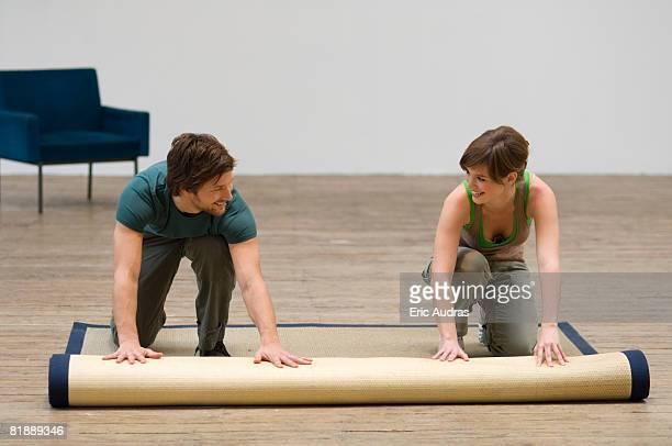 Couple unrolling a carpet on a hardwood floor