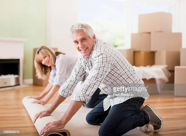 Paar unrolling Teppich in neues Haus