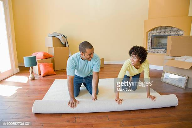 Couple unrolling carpet in unfurnished room