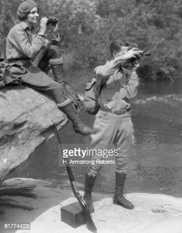 Couple upland hunt near streamside, with field glasses and gun. : Foto de stock