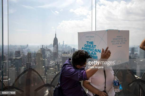 A couple use a viewing box during the solar eclipse at 'Top of the Rock' observatory at Rockefeller Center August 21 2017 in New York City While New...