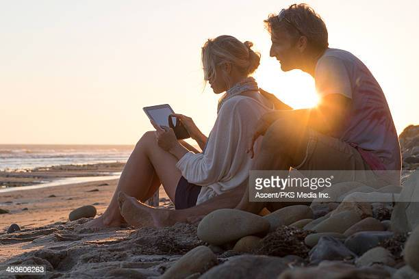 Couple use digital tablet together, at beach
