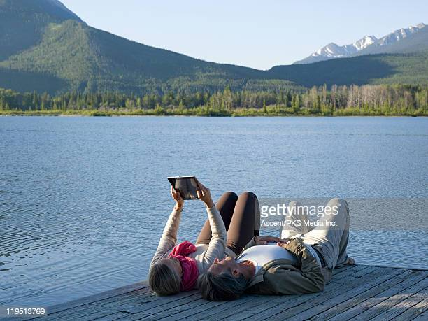 Couple use ipad on wharf edge, mountain lake